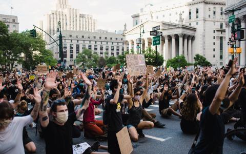 Protesters kneeling and holding their hands in the air